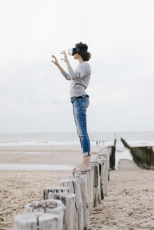 Woman standing on wooden stake on the beach wearing VR glasses - KNSF02622