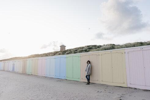 Woman leaning against beach hut - KNSF02625