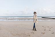 Happy woman standing on the beach - KNSF02628