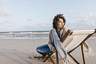 Woman sitting on deckchair on the beach - KNSF02634