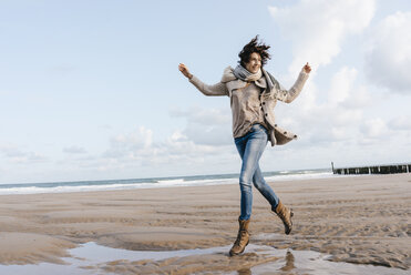 Happy woman running on the beach - KNSF02643