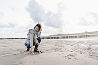 Woman crouching on the beach drawing a heart in the sand - KNSF02646