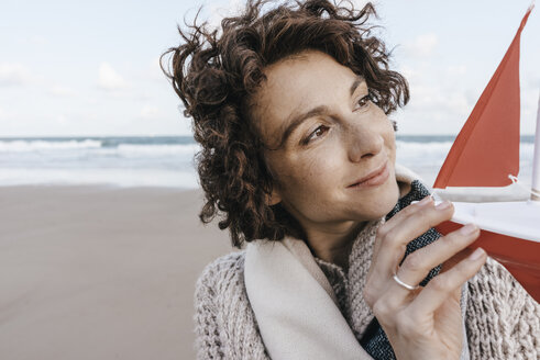 Portrait of smiling woman holding toy boat on the beach - KNSF02649