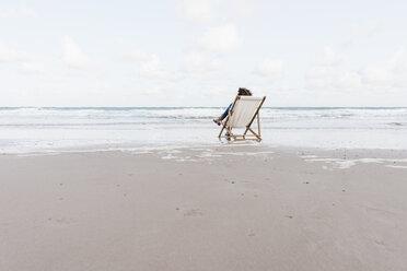 Woman sitting on deckchair on the beach - KNSF02652