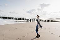 Woman walking on the beach - KNSF02655