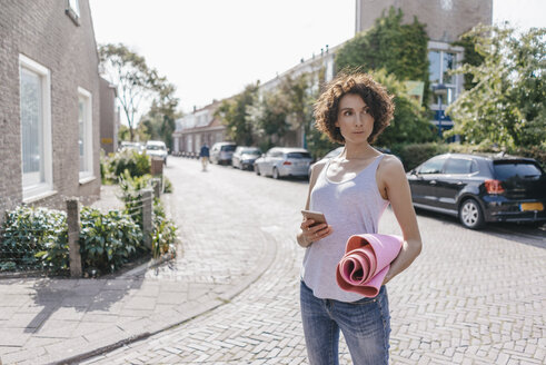 Woman with cell phone and mat on a road - KNSF02679
