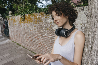 Woman with headphones and cell phone on pavement - KNSF02682