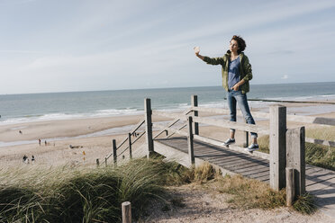 Woman standing on boardwalk at the beach taking a selfie - KNSF02688