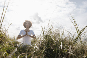 Woman practicing yoga in beach dune - KNSF02694