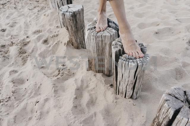 Woman's feet walking on wooden stakes on the beach - KNSF02697