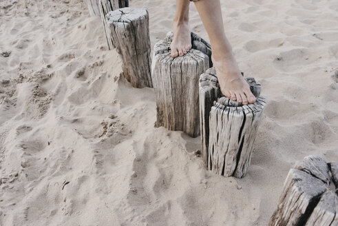 Woman's feet walking on wooden stakes on the beach - KNSF02697