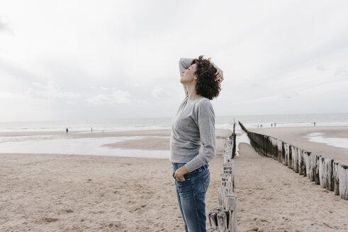 Woman standing on the beach - KNSF02700