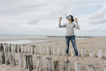 Woman standing on wooden stakes on the beach wearing VR glasses - KNSF02703