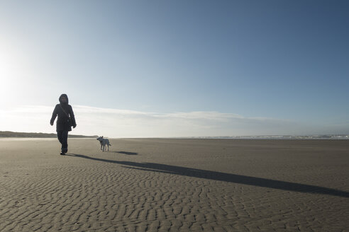Germany, Lower Saxony, East Frisia, Langeoog, woman with dog on the beach - JATF00971