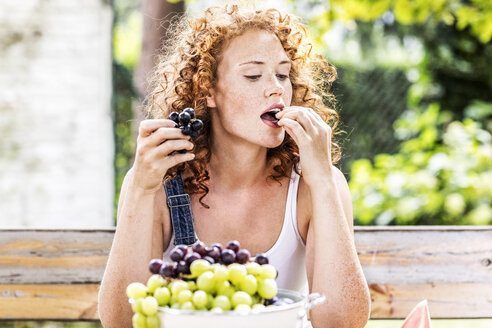 Portrait of redheaded young woman eating grapes - FMKF04422