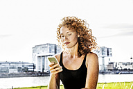 Germany, Cologne, portrait of serious young woman looking at cell phone - FMKF04431