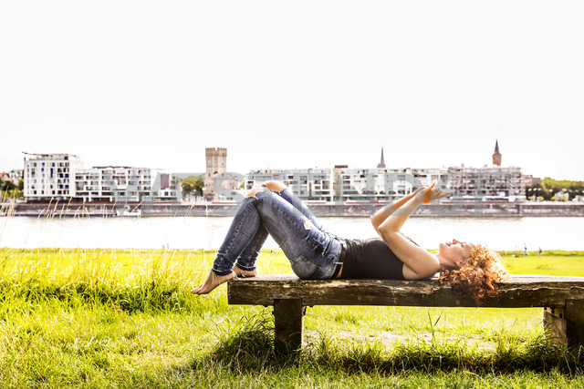 Germany, Cologne, redheaded young woman lying on bench taking selfie with cell phone - FMKF04434