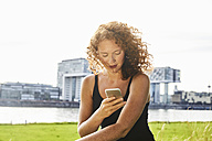 Germany, Cologne, redheaded young woman using cell phone - FMKF04437