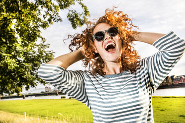 Germany, Cologne, portrait of screaming redheaded young woman wearing sunglasses - FMKF04440