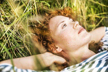 Portrait of young woman relaxing on a meadow - FMKF04446