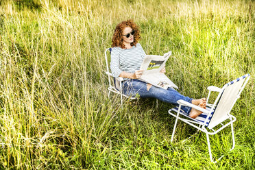 Young woman relaxing on a meadow reading newspaper - FMKF04449
