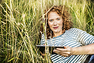 Portrait of smiling young woman relaxing on a meadow with tablet - FMKF04452