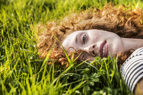 Portrait of redheaded young woman lying on meadow - FMKF04461