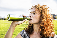 Portrait of redheaded young woman drinking beverage - FMKF04464