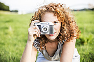 Young woman on a meadow taking picture of viewer with camera - FMKF04467