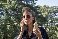 Young woman with ice cone using smartphone - LMF00750