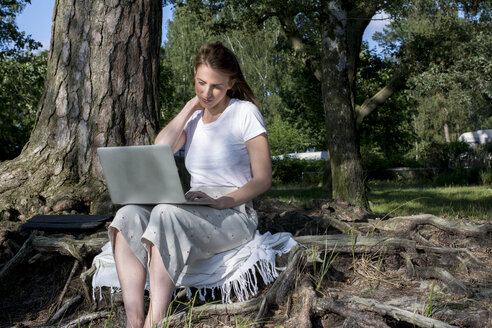 Young woman using laptop in the woods - LMF00753