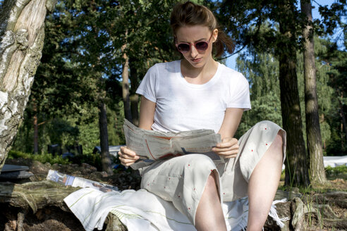 Woman sitting in the woods reading newspaper - LMF00756