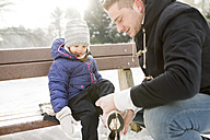 Father helping daughter to put on her ice skates - HAPF02101