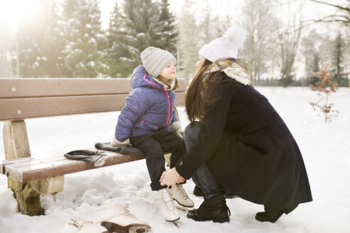 Mother helping daughter to put on her ice skates - HAPF02104