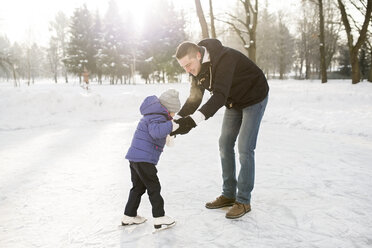 Father and daughter ice skating on frozen lake - HAPF02110