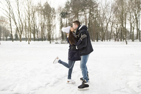 Couple ice skating on a frozen lake, kissing and embracing - HAPF02113