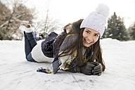 Woman with ice skates lying on snow - HAPF02119