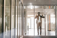 Businessman standing in office building, looking through VR goggles - KNSF02716