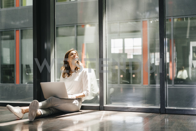 Businesswoman sitting on ground in empty office, using laptop - KNSF02734