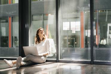 Businesswoman sitting on ground in empty office, using laptop - KNSF02734