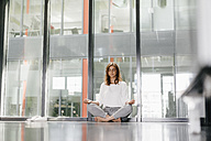 Businesswoman practicing yoga in office, meditating - KNSF02737
