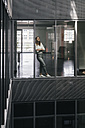 Woman standing at office window, looking up, smiling - KNSF02740
