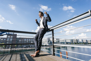 Happy businessman standing on balcony, with arms out - KNSF02776