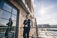 Pensive businessman standing on balcony - KNSF02779