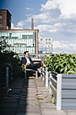Businessman relaxing in his urban rooftop garden - KNSF02782
