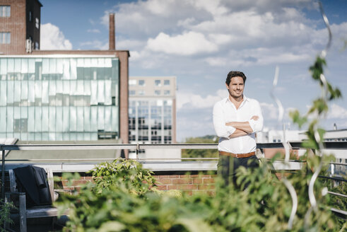 Businessman cultivating plants in his urban rooftop garden - KNSF02785