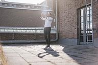 Businessman standing on rooftop terrace, taking a selfie - KNSF02791