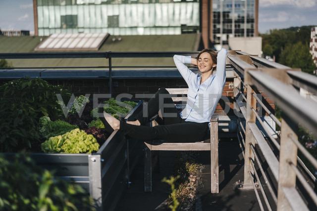 Businesswoman relaxing in his urban rooftop garden - KNSF02794