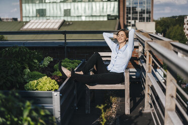 Businesswoman relaxing in his urban rooftop garden - KNSF02794