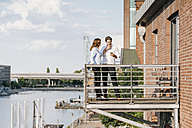 Business people standing on balcony, using smartphone - KNSF02803